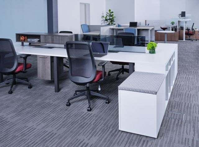 Oxygen Benching with glass screen, worksurface mounted storage, and suspended pedestal. Shown with Bolton Seating